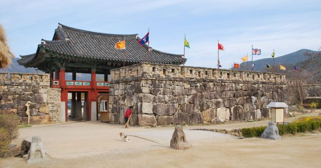 Entrance to Nagan Fortress Folk Village, a large stone wall, with flags in front of a traditional building of red wooden pillars, turquoise paintings and a dark roof. In front is a stone courtyard with small stone statues and a woman sweeping the ground.
