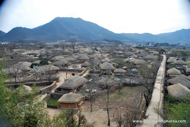 View over Nagan Fortress Folk village, lots of traditional huts with thatched roofs, and the mountains behind, in soft focus.
