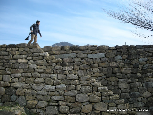A man walks on a large stone wall at Nagan Fortress, with blue sky and a mountain in the background.