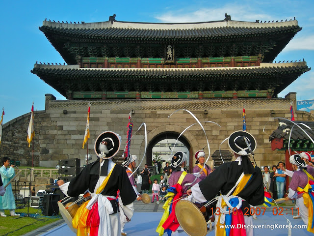View of the historic grand gate, Sungnyemun at Namdaemun traditional market. The imposing building is built of stone, with an archway, and an ornate roof. Traditional dancers and a marching band in the foreground, brightly dressed.