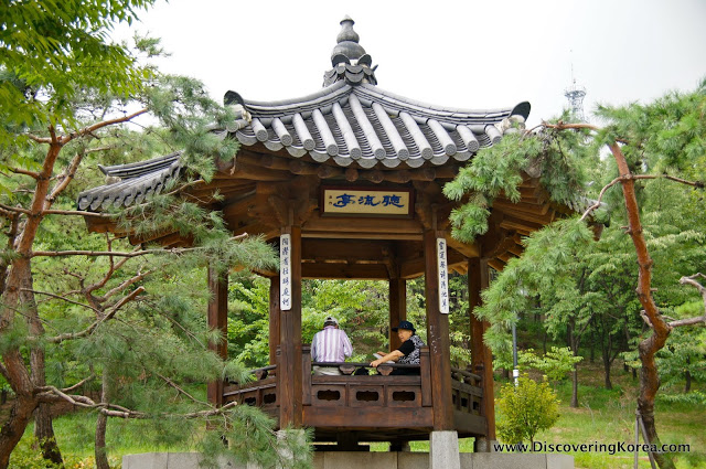 A pergola in Namsan botanical garden. Wooden house with ornate roof and open sides, on a stone plinth surrounded by trees. Two people are sitting in the pergola.