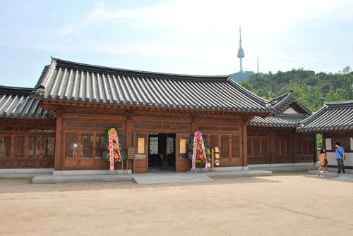 The exterior of Namsangol Hanok village, a brown wooden building with a grey roof, Seoul's tower in the background. Two people to the right, on the stone steps.