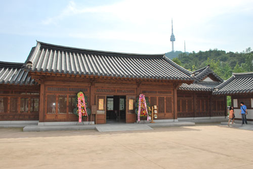 Outside view of Namsangol Hanok, a brown wooden building with open doors and flower decorations outside. Two people to the right of the frame and soft focus tower and vegetation in background.