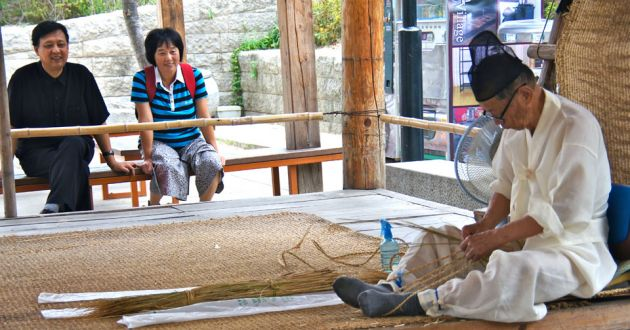 A Korean man, dressed in white, with a black hat, weaving reeds while sitting on the floor at Namsangol village, in the background are two tourists looking on.