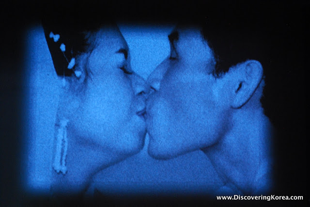 A photograph with a blue overlay of a man and a woman kissing, just their heads are visible in the frame.
