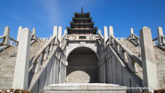 External view of the National Folk Museum of Seoul, a large imposing concrete building with ornate curved roof on four different levels, the center of the frame shows stairs leading up to the arched entranceway, either side are stairs leading up beside it, with a blue sky background in bright sunshine.