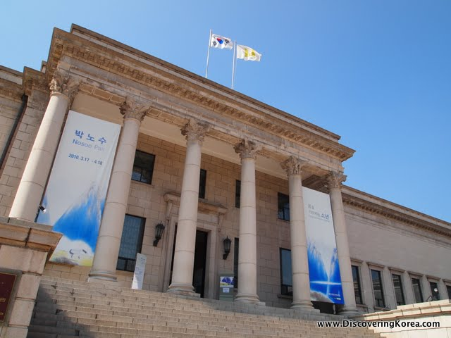 Stone building with four large pillars forms part of the national museum of art. Wide steps leading up to the two story doorway and ornate roof, with two flags on top. Blue sky behind.