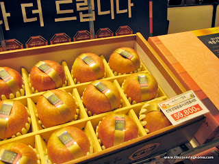 A box with partitions, each section containing an apple, with a label around it. In the foreground is a printed label showing the price.