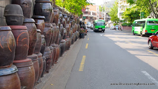 A street in Noksapyeong, with green buses on the right of the frame on a tarmac road, and on the left a long line of large ceramic pots stacked on top of each other.