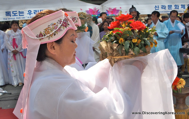 A Korean woman, dressed in white robes, with a pink and white floral hat holding a pot of red roses and yellow flowers. In the background crowds are watching at the Lotus Lantern Festival in Seoul.