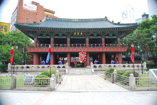 Stone steps leading up to a large building with red pillars and a traditional curved roof, painted in ornate turquoise in the eaves, lawn either side, and flags.