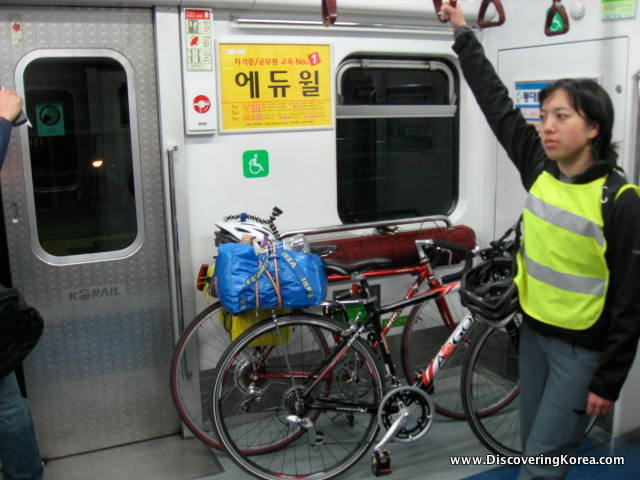 A woman rides the subway with two bicycles, the background is the subway doors and Korean signs.