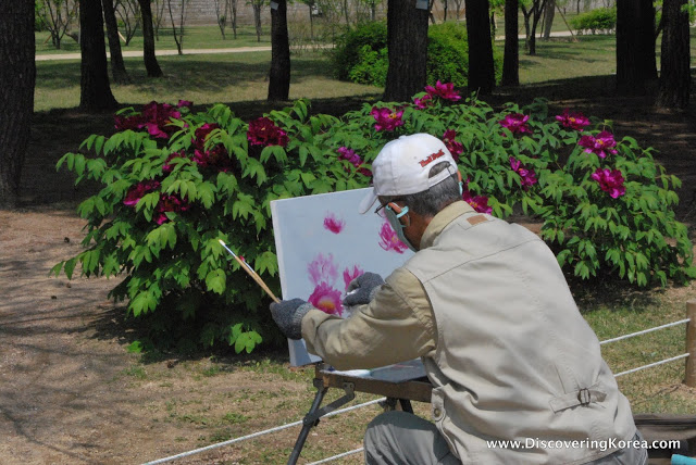 A man with an easel and a paintbrush, painting a bush of pink flowers in the foreground. Behind is a green bush with pink flowers in a forest.