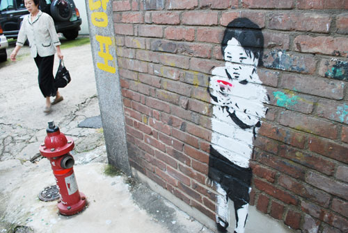 A brick wall with a painting of a child holding a gun, the painting is mostly white, with the child's hair in black. To the left is a red fire hydrant and a pedestrian in the background.