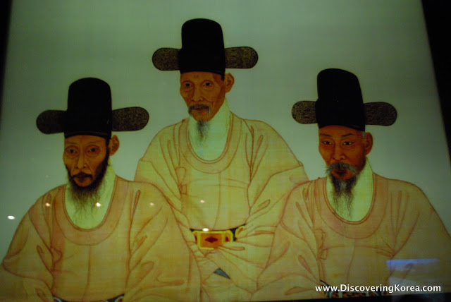 A painting of three elderly men, dressed in yellow robes, with black hats and long straggly beards.