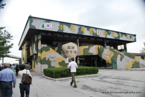 Outside the Dora Observatory in DMZ, the building painted green and yellow camouflage with pedestrians on the left of the frame.
