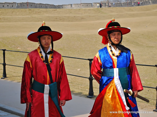 Two people in traditional Korean dress, red, yellow and blue, wearing hats walk along a path with a sandly backdrop and buildings behind.