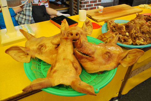 Four pig's heads arranged on a green plastic dish, on a yellow wooden surface, with cooked meat on a blue plastic plate to the right of them.
