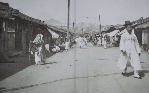 A black and white historical photo of people walking in a street in old Seoul, with traditional houses either side.