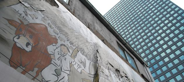 To the left of the frame is a painted concrete wall, showing a man with a cow, to the right of the frame is a glass high rise modern building in Seoul.