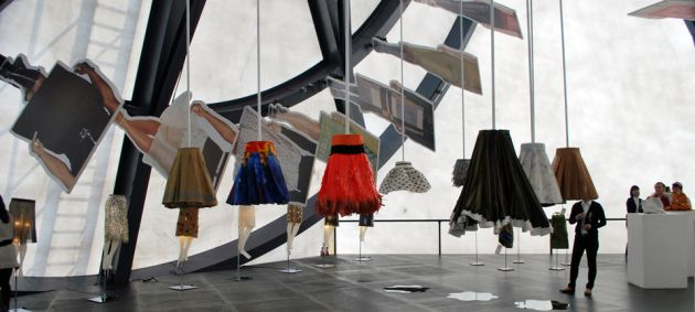 An exhibition of skirts hanging from the ceiling, against a white and black background at the Prada transformer in Seoul.