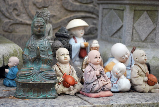 A collection of religious dolls on a stone surface.