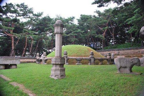 A circular mound covered in grass, surrounded by stone pillars and stone carvings of animals housing Queen Jeonghyeon's tomb. In the background is a pine forest.