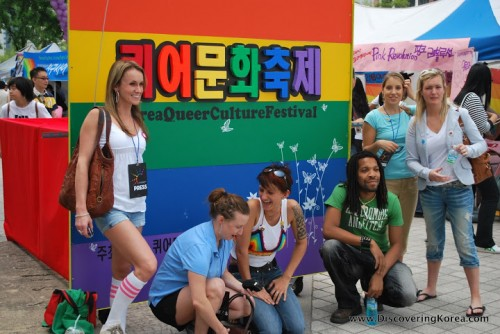 A group of young people pose in front of a rainbow colored sign, to the left of the frame a woman is standing, in the center three are kneeling, and to the right two women are standing.