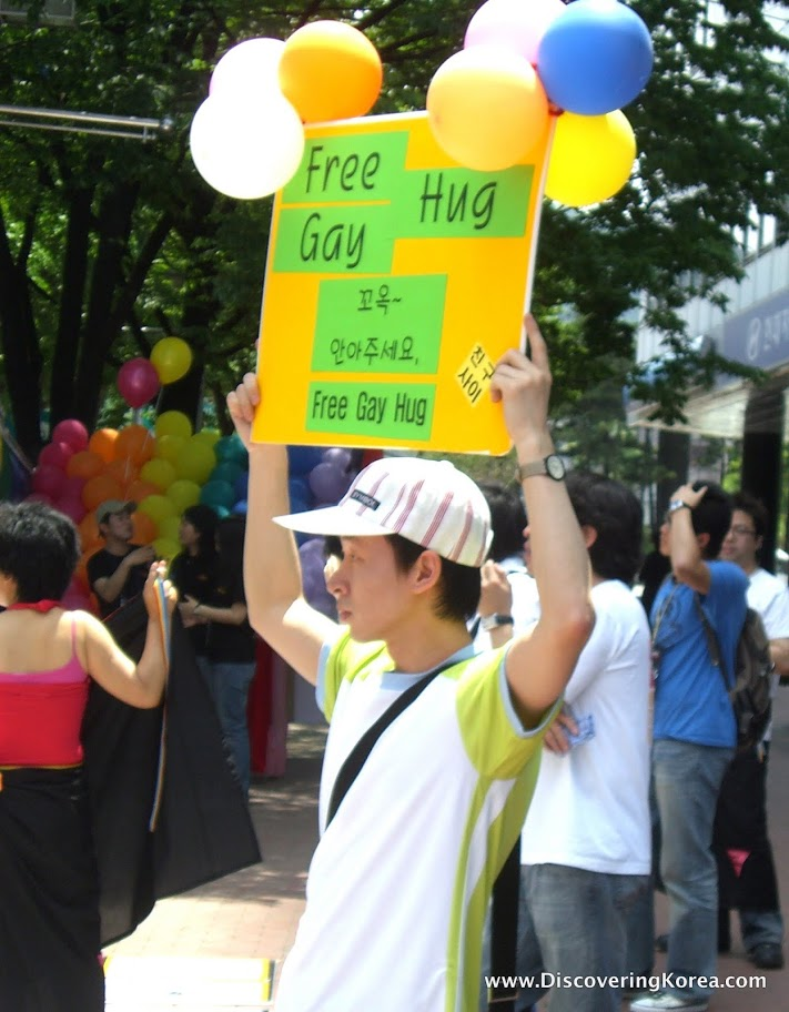 A young man with a white and green t shirt holds up a yellow banner with black writing on a green background and balloons, amongst a crowd of people at Queer Culture Seoul.