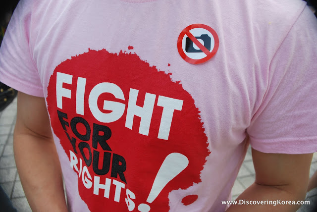 Close up of a man's t shirt, a light pink color, with a red splash and white and black text, and a sticker in white, black and red.