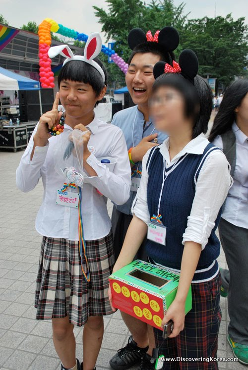 Three young Korean girls dressed in white shirts and plaid skirts, all wearing bunny ears and holding a red and green box.