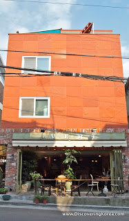 An orange building with two windows and an open storefront, showing table and chairs in sunshine.
