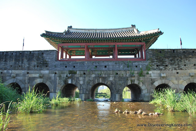 A stream runs under arches below the walls at Suwon fortress. An ornate roof with red and blue coloring at the top of the frame, and river vegetation to the left and right.