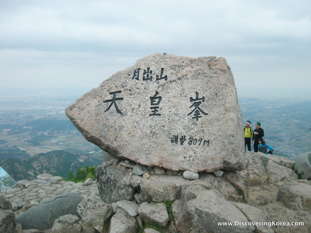 Large rock sign with Korean lettering, two hikers to the right of the frame and in the background, looking down in the distance over grassland and farms.