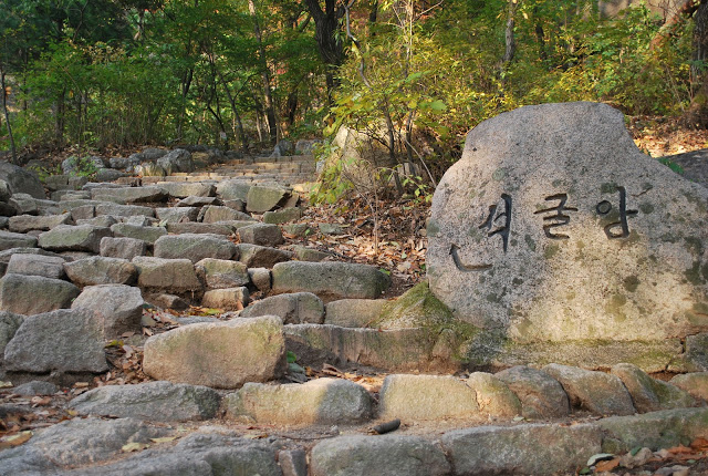 Rocky steps into a forest and a large rock with Korean inscription to the right of the frame.