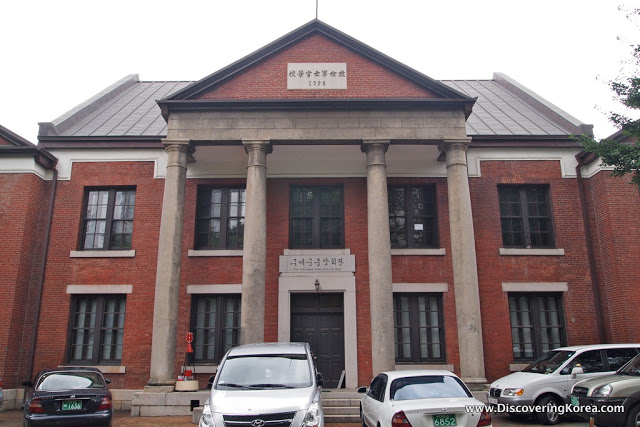 Red brick building with stone pillars at the front, with cars parked. Housing the Russian embassy in Seoul.
