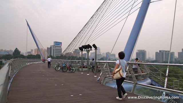 Looking across the Saetgang bridge, brown wooden walkway, with metal frame to either side, two people walking towards the city, with bicycles in the center of the frame.