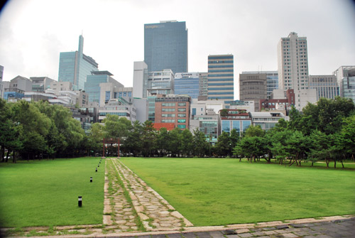 View over a stone pathway with grass and trees either side, towards the city buildings in Seoul.