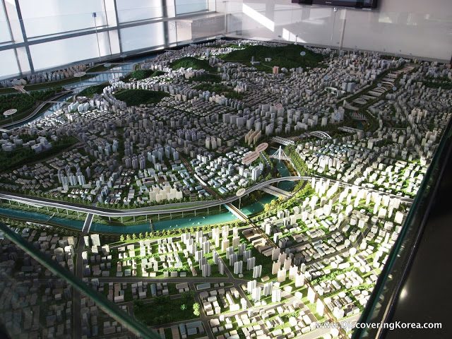 A scale model of the transformation of Cheonggyecheon area, Seoul. Small buildings and roads, with bridges across the river are are shown to scale, with green spaces in between, at Cheonggyecheon Museum.