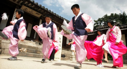 Traditional Korean dancers, in pink with black waistcoats perform a traditional Seollal dance outside a building.