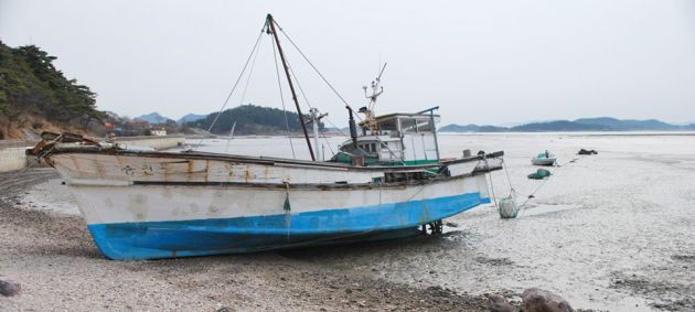 A blue and white boat, out of the water at low tide, on a shingle beach at Seonyudo Island, Jeolla.