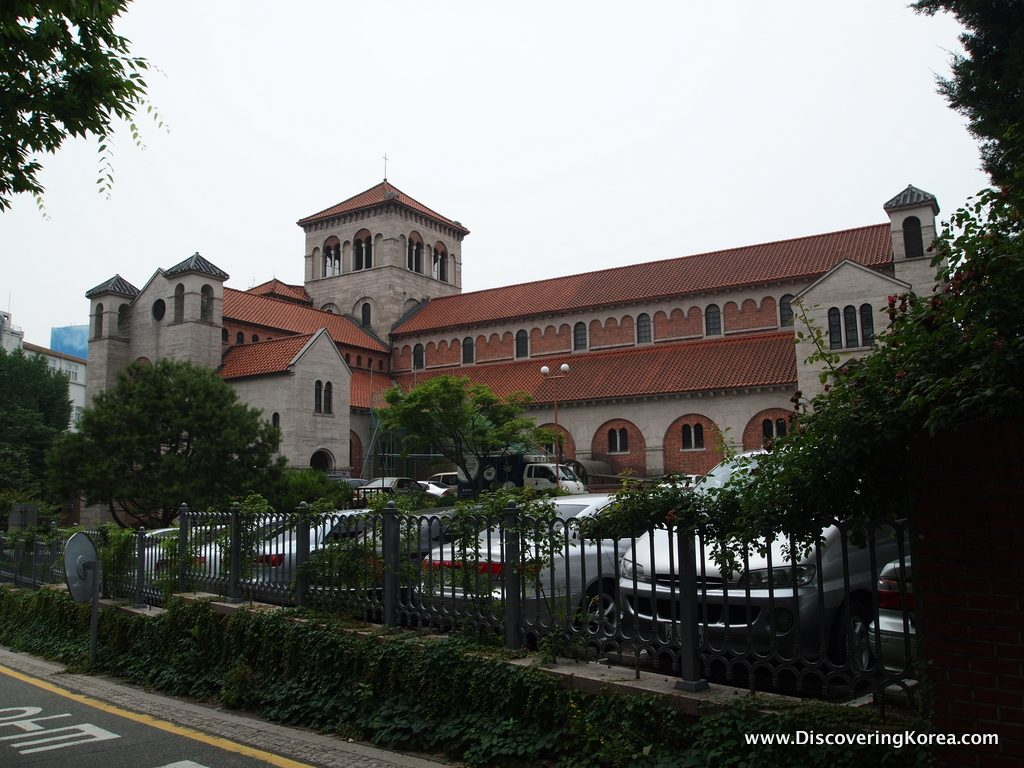 A large stone building with a red tiled roof, the Seoul Anglican cathedral with cars parked in front, metal railings with creeping plants, on a cloudy day.