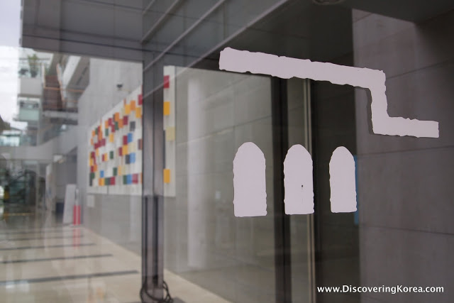 Inside the Seoul Art Museum, pictured through glass doors, a multicolored piece on the wall, grey tiled background.