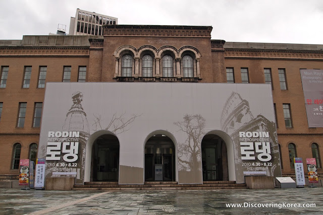 Outside view of the Seoul Art Museum, an imposing two storey stone building with archway doors.