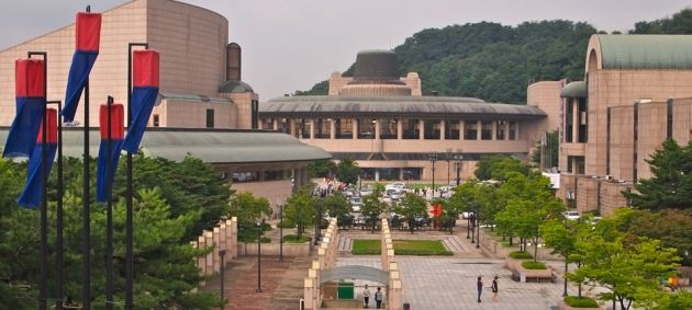 The pale red brick building of the Seoul Arts Center, with a courtyard in front, some green trees and red and blue flags.