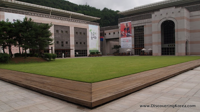 An external view of the pink and white stone Seoul Arts Center, with a green grass lawn in front.