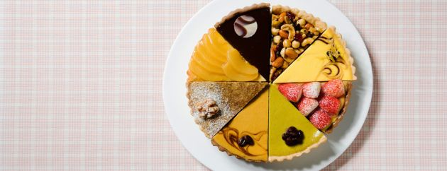 A pastry tart, cut into eight slices, each slice being different, as though made into a collage, on a white plate and a pink and white checked background.
