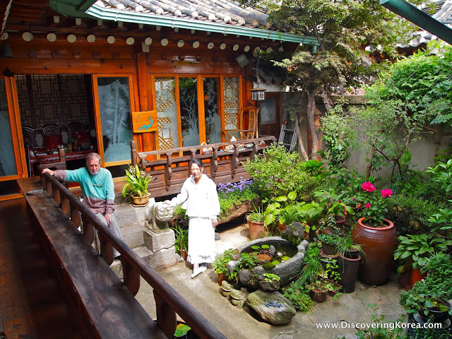 An L-shaped home in Bukchon Hanok village, showing a courtyard containing pots planted with flowers and green vegetation. To the center of the frame is the wooden house showing windows opening onto a verandah.