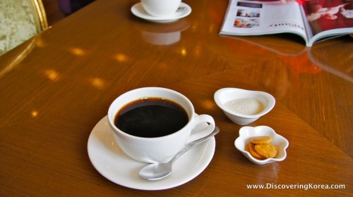 A wooden table with a white cup containing black coffee, a spoon, and a bowl of sugar and a small bowl of cookies.