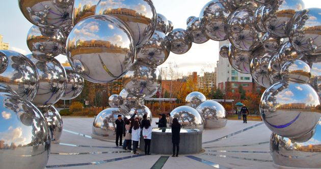 An outside modern art exhibit made with connected bubble-like stainless balls. A group of Korean high school students gathers underneath.